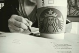 Close-up of Starbucks coffee cup with a student doing homework in the background