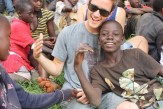 College student from CSUSM sitting among children from Ugandan village