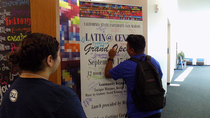 Student sign grand opening poster and visit the new facility.