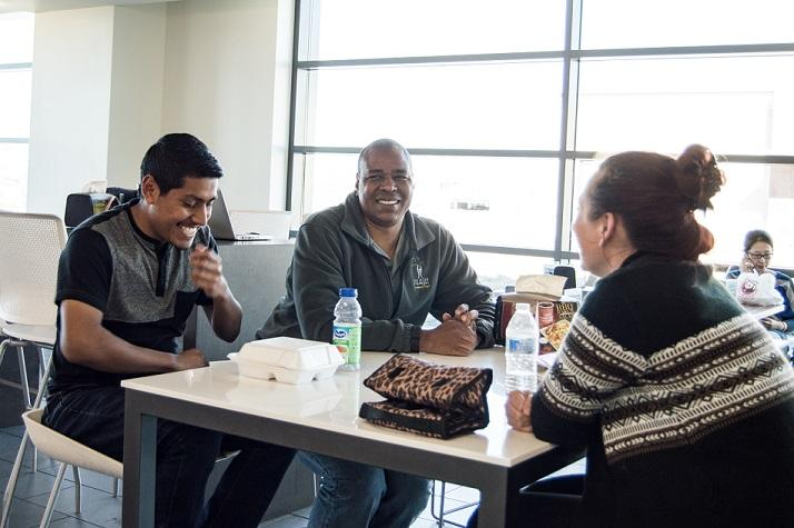 Students, Jaciel, Damon & Adara laugh over a meal together in the USU dining hall.