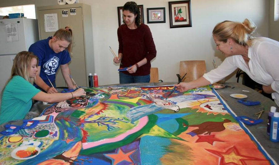 CSUSM Human Development students (from left to right) Lauren, Nicole and Emily, and Dr. Eliza Bigham (far right) help paint a mural for Operation Art at one of their biweekly Friday meetings.