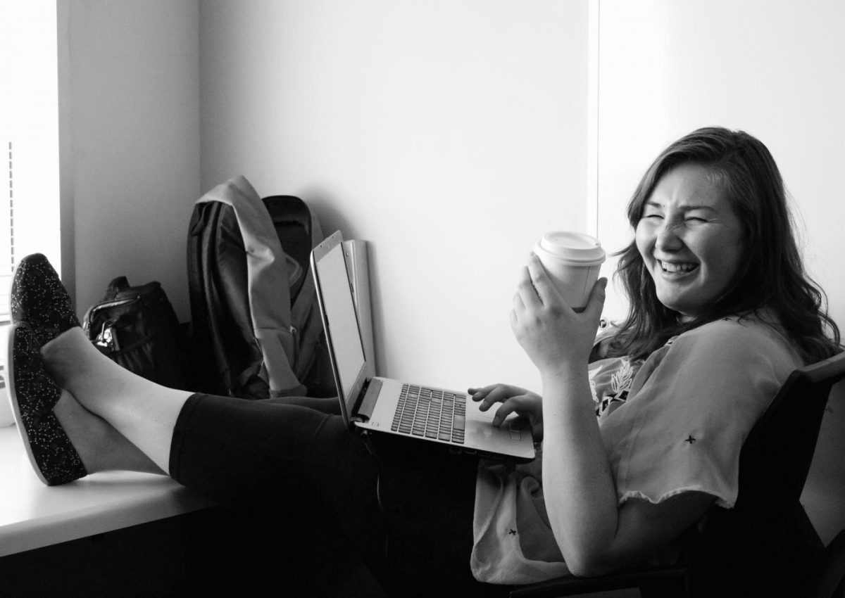 Meghan+enjoying+her+coffee+in+the+Cougar+Chronicle+office+where+she+feels+right+at+home.