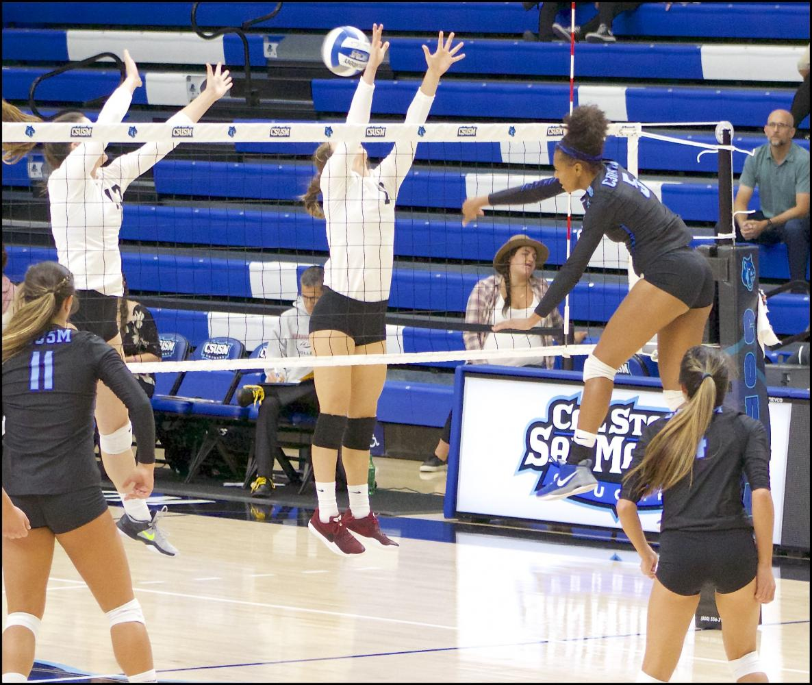 Outside hitter Micah Hébert spikes the ball right through Chico State's defense, scoring for CSUSM.