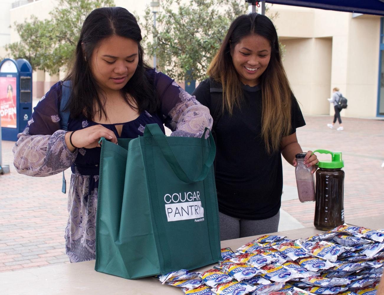 Cheryl Corpuz and Creska Radoc collect food for the  Cougar Pantry held on September 21.