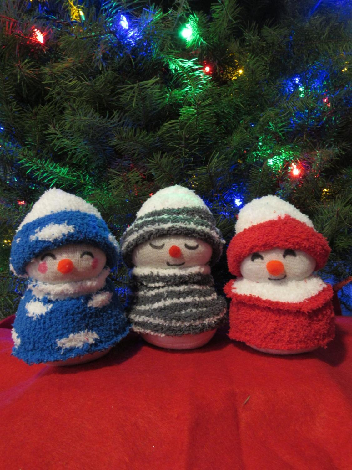 Inexpensive sock snowman under the christmas tree adds a perfect christmas magic.