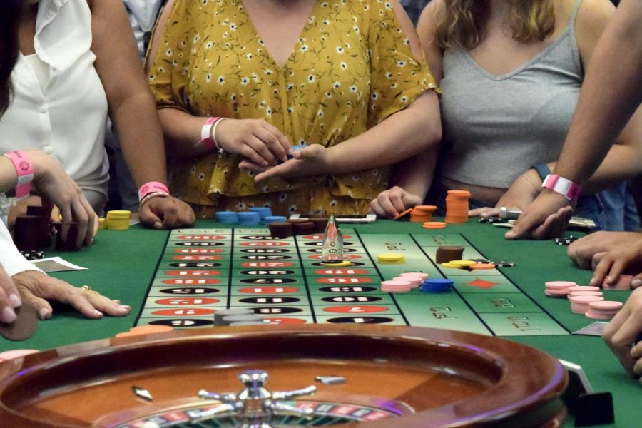 Students place their bets at the roulette table during CSUSM's