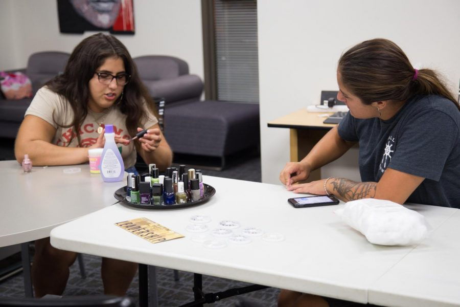 Alexis VanPelt and Natalie De La Rosa  get to know each other as they paint their nails in the Gender Equity Center on August 30.