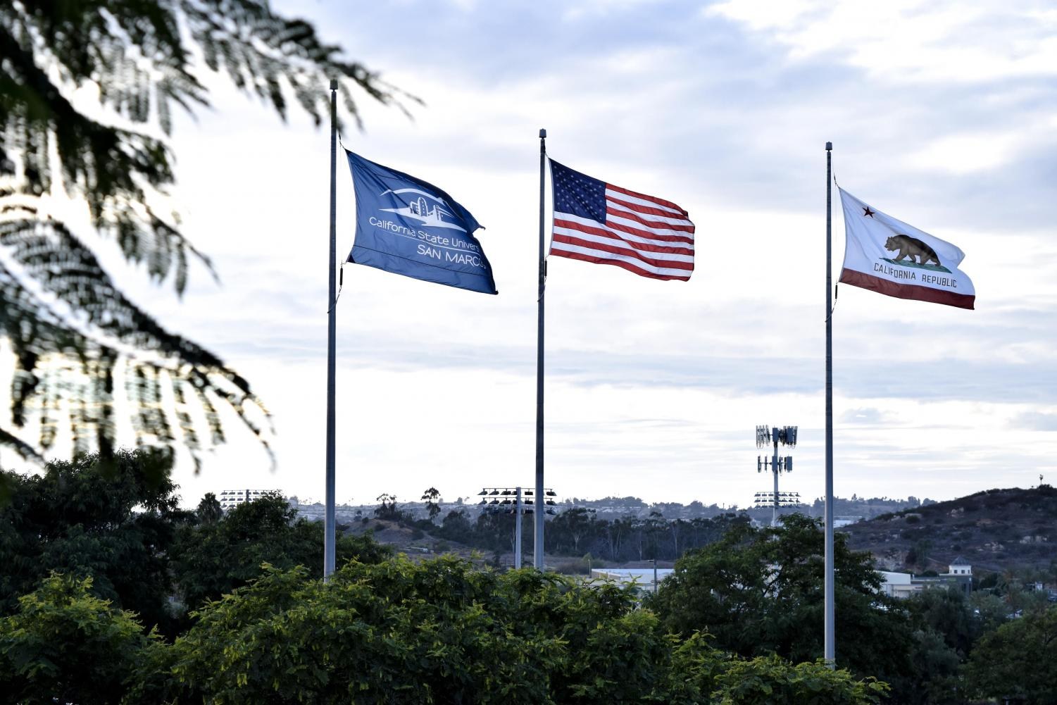 The American flag flies high in front of the CSUSM campus.