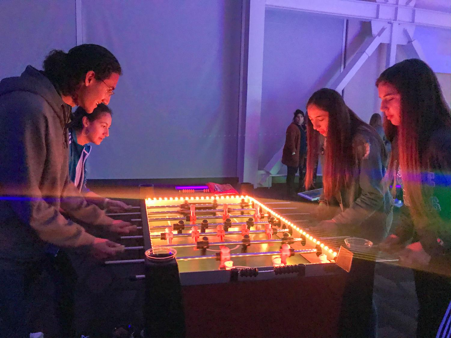 Students go head to head in a game of foosball.