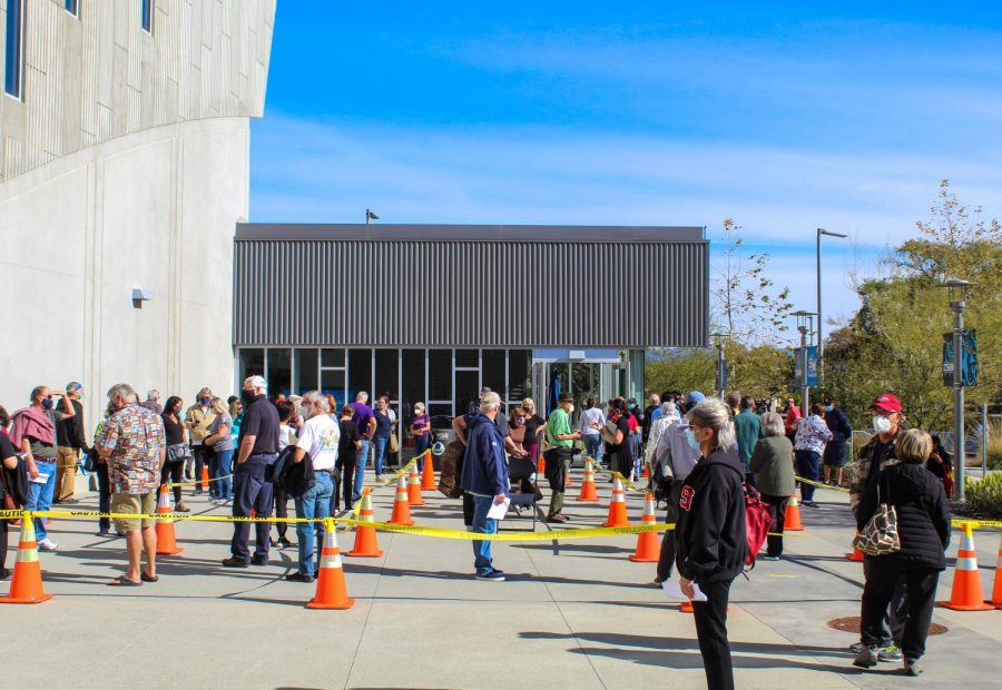 People wait in line to get a COVID-19 vaccine at the CSUSM Sports Center on Jan. 31.